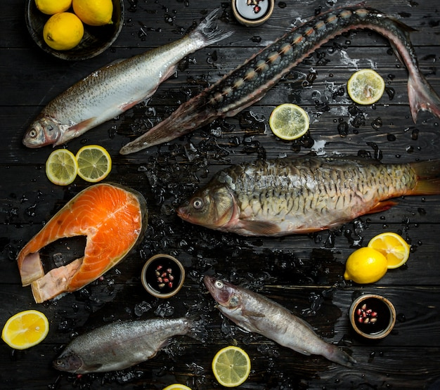Raw fish sorts on a black wooden table with lemon slices around. Free Photo