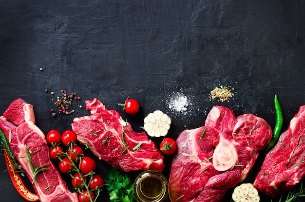 Raw fresh meat steak with cherry tomatoes, hot pepper, garlic, oil and herbs Premium Photo
