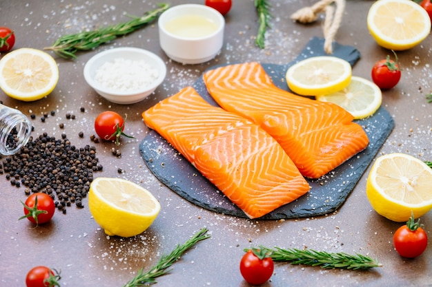 Raw and fresh salmon meat fillet on black stone slate Free Photo