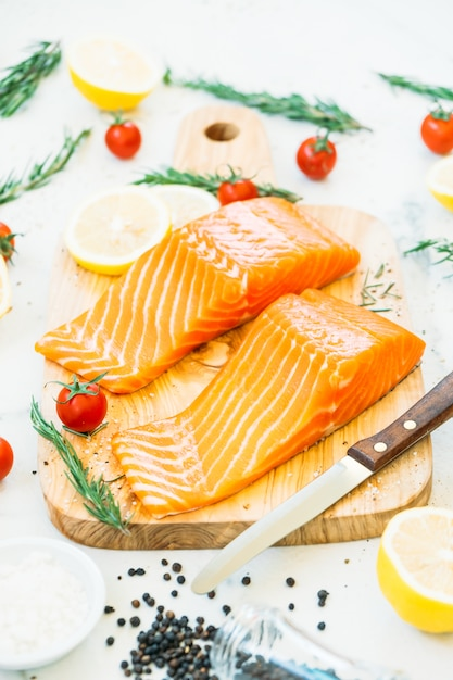 Raw and fresh salmon meat fillet on wooden cutting board Free Photo