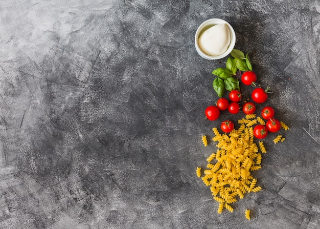 Raw fusilli with cherry tomatoes; basil leaves; black pepper and cheese on texture background Free Photo