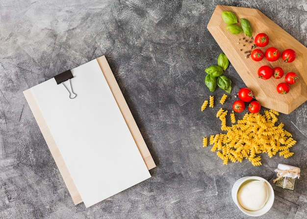 Raw fusilli with ingredients and blank paper on clipboard over the grunge background Free Photo