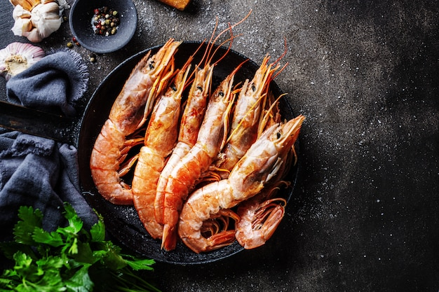 Raw giant shrimps on dark table Free Photo