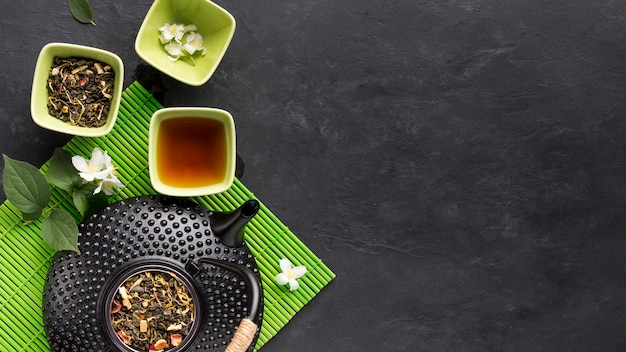 Raw herbal tea ingredient with teapot on green placemat over black surface Free Photo