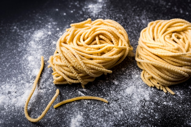 Raw homemade capellini pasta nest with flour on a black background Free Photo