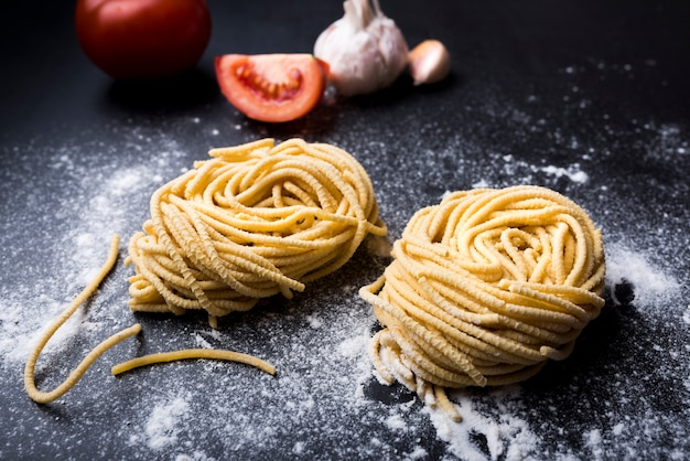 Raw homemade pasta nest on flour with garlic and tomato at background Free Photo