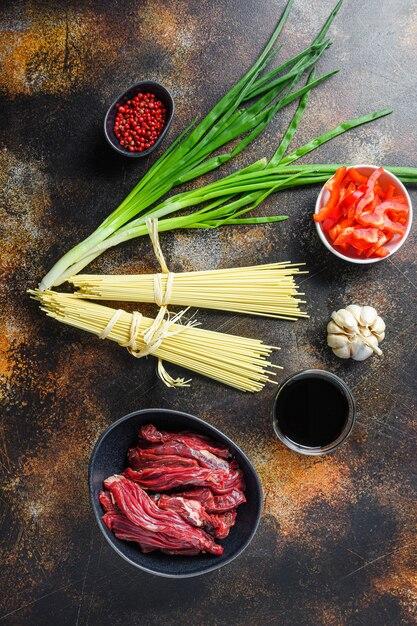검은 그릇에 야채와 쇠고기를 곁들인 볶음면의 원재료. 오래 된 시골 풍 테이블. 프리미엄 사진