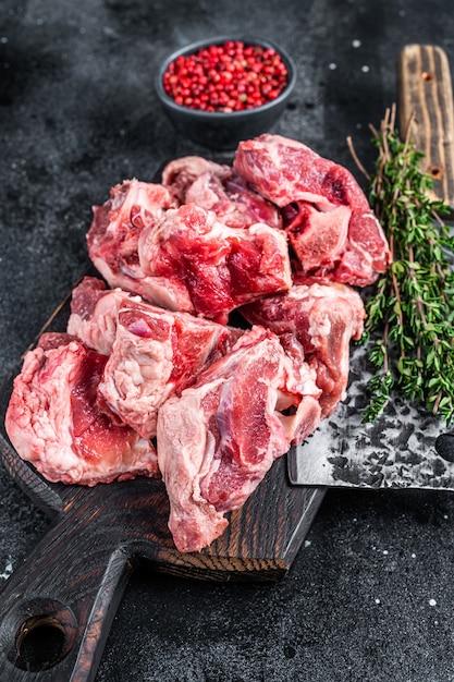 Сырое тушеное мясо ягненка с косточкой на деревянной доске мясника и тесаке. чернить Premium Фотографии