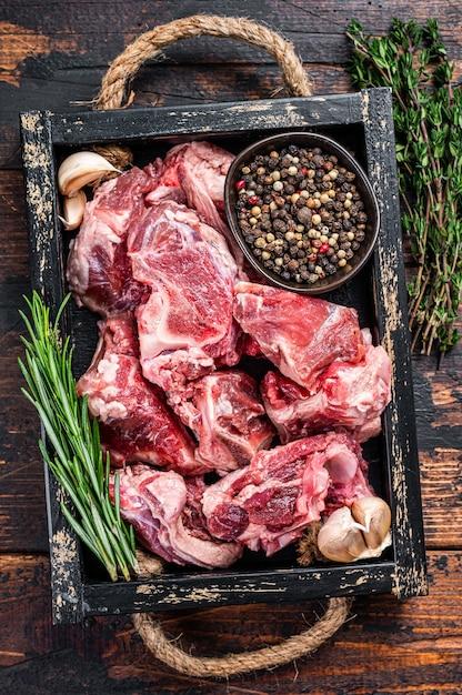 Сырое мясо ягненка или козлятины, нарезанное кубиками для тушения с косточкой. темное дерево Premium Фотографии