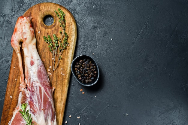 Raw leg of goat on a wooden cutting board. rosemary, thyme, black pepper. Premium Photo