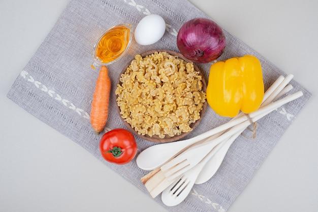 Maccheroni crudi con le verdure sul piatto di legno sulla tovaglia Foto Gratuite