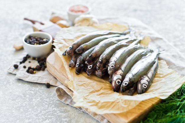 Raw mackerel on a wooden chopping board, dill, pink salt, pepper and garlic. Premium Photo