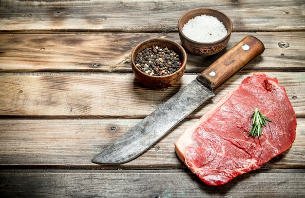 Raw marbled beef steak with spices on wooden table. Premium Photo