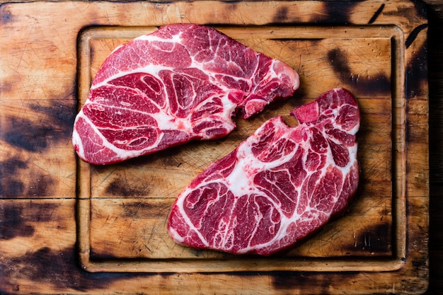 Raw marbled beef steaks on wooden cutting board Premium Photo