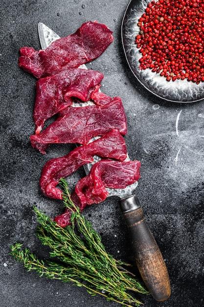 Сырое мраморное мясо нарезать тонкими полосками для бефстроганова Premium Фотографии