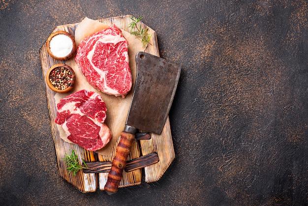 Raw marbled ribeye steak and butchers knife Premium Photo