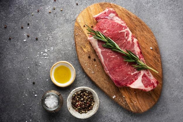 향신료와 기름 나무 보드에 생고기 쇠고기 스테이크 프리미엄 사진