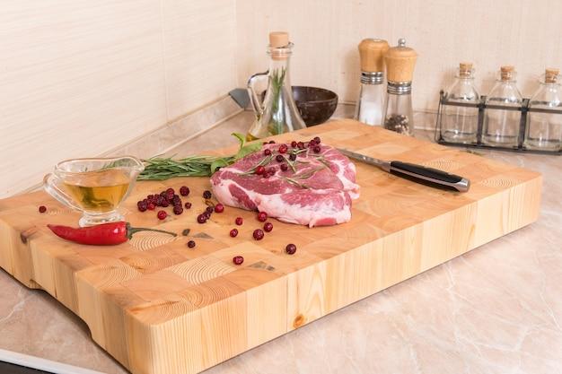 生肉。木の板にスパイス、ベリー、オイルを添えたポークステーキ Premium写真