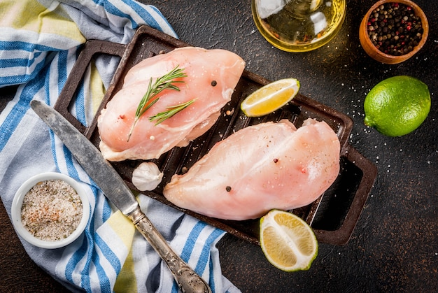 Raw meat ready for grill or barbeque chicken breast filet with olive oil herbs and spices on dark rusty background Premium Photo