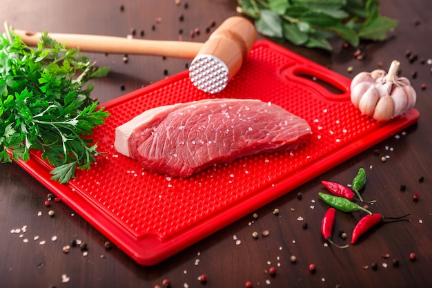 Raw meat selection on wooden cutting board Premium Photo
