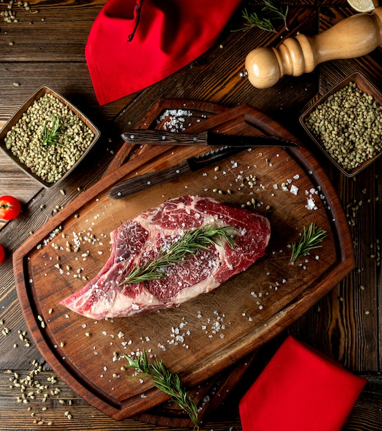 Raw meat slice topped with herbs and salt Free Photo