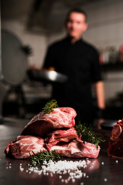 Raw meat steaks with ingredients on table Free Photo