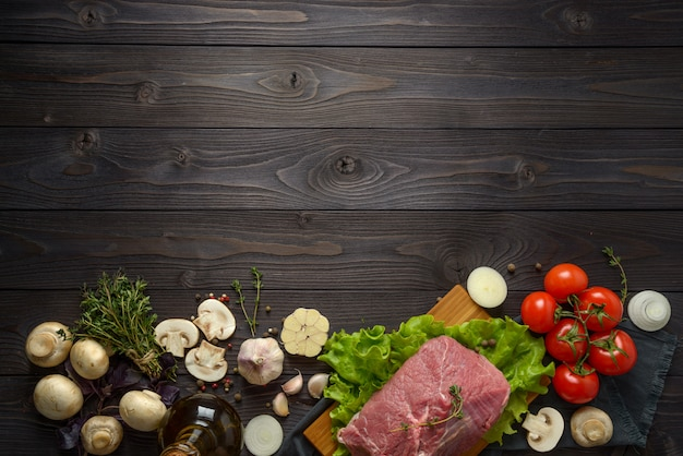 Raw meat with ingredients on a wooden table Premium Photo