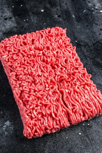Сырой фарш из говядины на кухонном столе. чернить Premium Фотографии