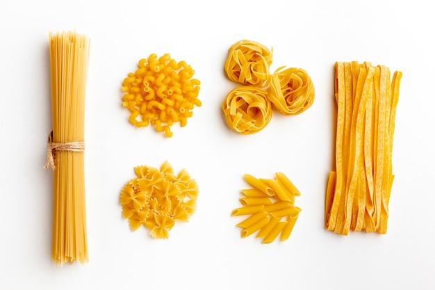 Raw mix of pasta on white background Free Photo