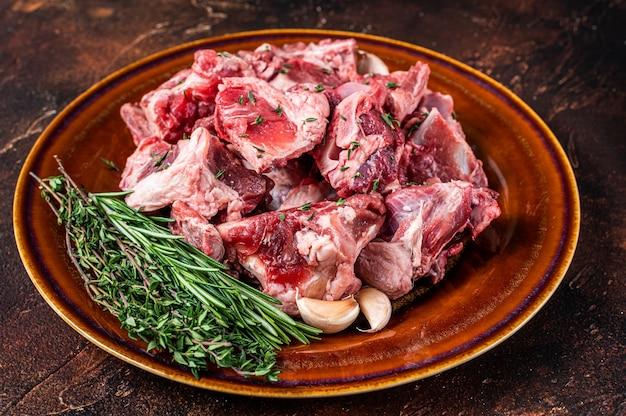 Сырое мясо баранины, нарезанное кубиками для гуляша или тушеного мяса с косточкой на деревенской тарелке. тьма Premium Фотографии