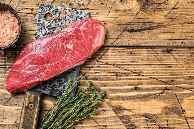 Сырой стейк из нью-йорка на тесаке, говядина. деревянный фон. вид сверху. скопируйте пространство. Premium Фотографии
