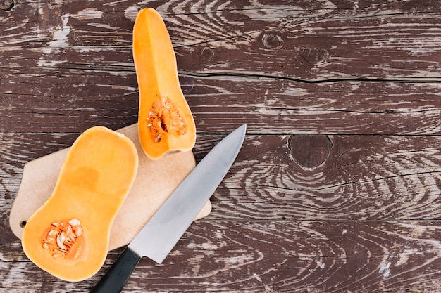 Raw orange organic butternut squash on chopping board with knife over the wooden desk Free Photo