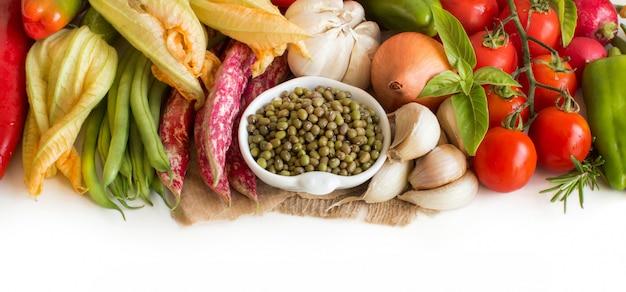 Сырые органические бобы маш в миске и сырые овощи Premium Фотографии
