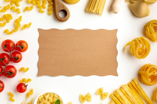 Raw pasta assortment and tomatoes with cardboard mock-up Free Photo