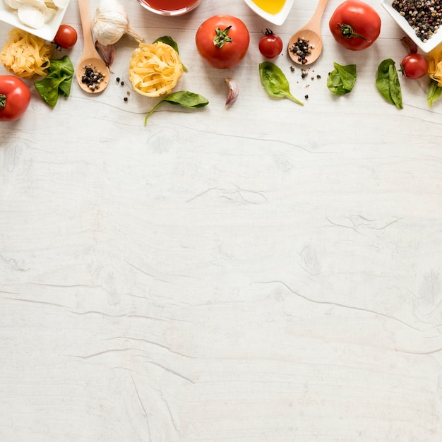 Raw pasta and it's ingredients arranged in row over white wooden table Free Photo