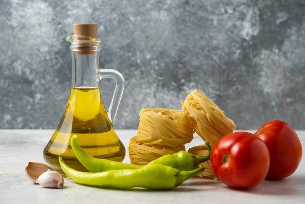 Nidi di pasta cruda, bottiglia di olio d'oliva e verdure sulla tavola bianca. Foto Gratuite