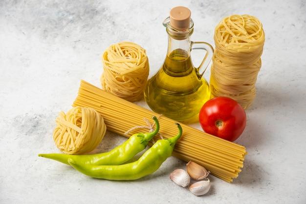 Nidi di pasta cruda, spaghetti, bottiglia di olio d'oliva e verdure su superficie bianca. Foto Gratuite