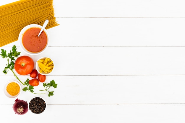 Raw pasta and tasty ingredient over white wooden table Free Photo