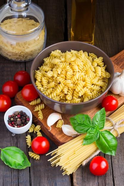 Сырая паста с помидорами черри и ингредиентами Premium Фотографии