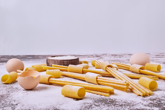 Raw pasta with flour and eggs onwooden table. Free Photo
