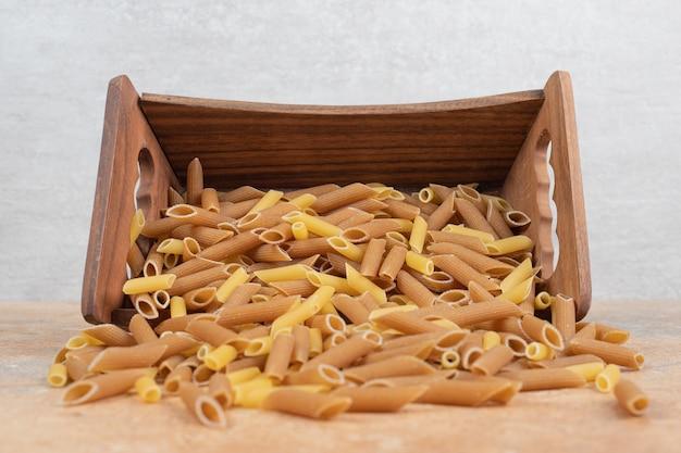 木製バスケットの生ペンネパスタ 無料写真