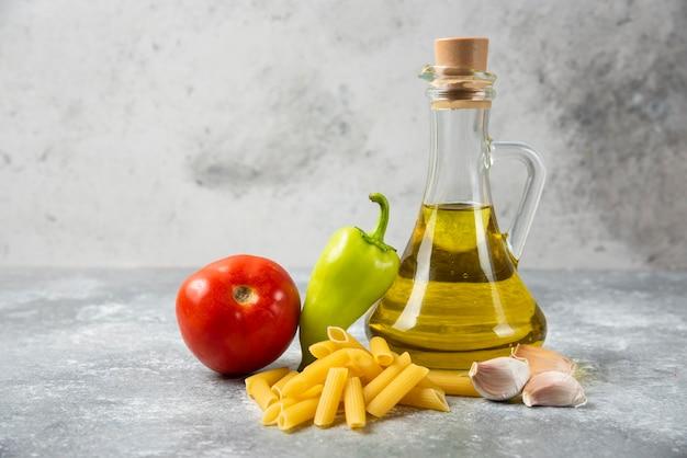 大理石のテーブルにオリーブオイルと野菜のボトルと生のペンネパスタ。閉じる。 無料写真