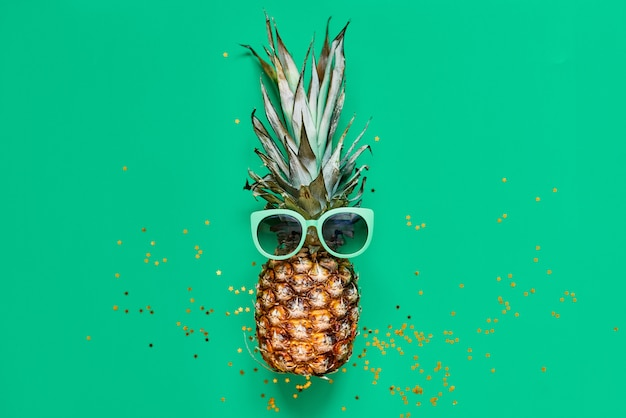 Raw pineapple with golden glitter. flat lay tropical concept Premium Photo