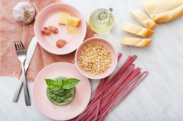 生のピンクのフェットチーネとペストソースと白い大理石のテーブルにピンクのプレートの成分 Premium写真