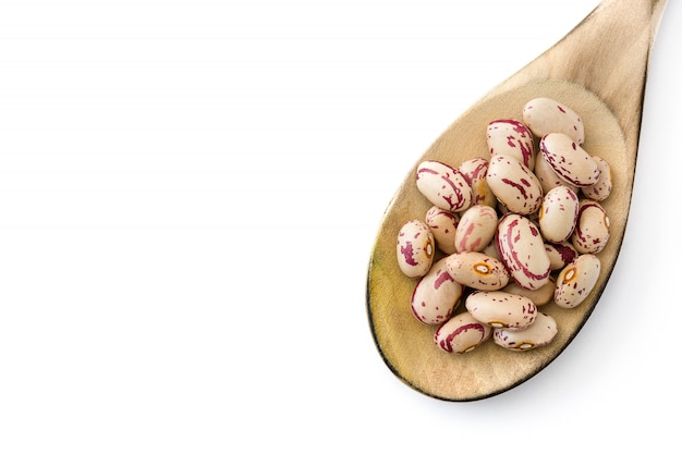 Raw pinto beans in wooden spoon isolated on white surface top view copy space Premium Photo