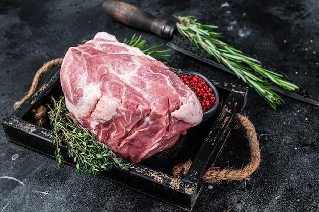 Кусок сырой свиной шеи для стейка chop на деревянном подносе с зеленью. чернить Premium Фотографии