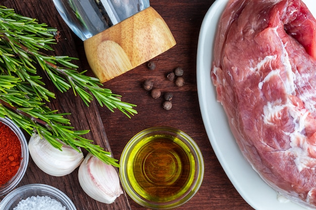 Raw pork tenderloin ready to roast, with spices (black pepper, olive oil, garlic, fresh rosemary, salt). . seen from above. Premium Photo