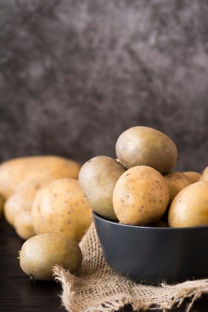 Сырой картофель в серой миске Premium Фотографии