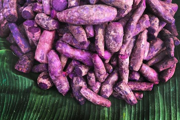 Сырой фиолетовый сладкий картофель на зеленом банановом листе свежий сладкий картофель сверху Premium Фотографии