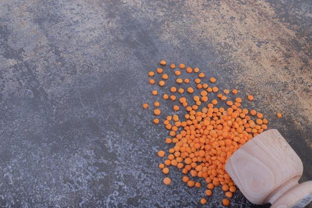 青の背景に木製のボウルに生の赤レンズ豆。 無料写真